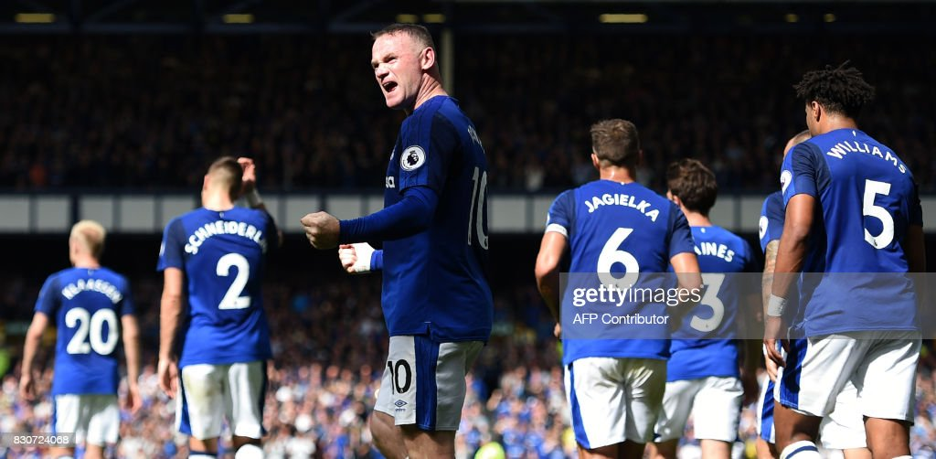 Everton's English striker Wayne Rooney (C) celebrates scoring the opening goal during the English Premier League football match between Everton and Stoke City at Goodison Park in Liverpool, north west England on August 12, 2017. / AFP PHOTO / Oli SCARFF / RESTRICTED TO EDITORIAL USE. No use with unauthorized audio, video, data, fixture lists, club/league logos or 'live' services. Online in-match use limited to 75 images, no video emulation. No use in betting, games or single club/league/player publications. /