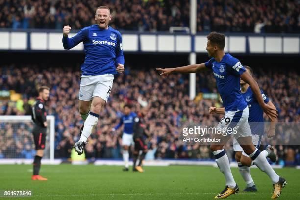 TOPSHOT Everton's English striker Wayne Rooney celebrates scoring the opening goal during the English Premier League football match between Everton...