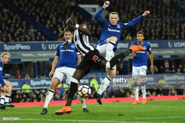Everton's English striker Wayne Rooney collides with Newcastle United's Senegalese midfielder Mohamed Diame to concede a corner during the English...