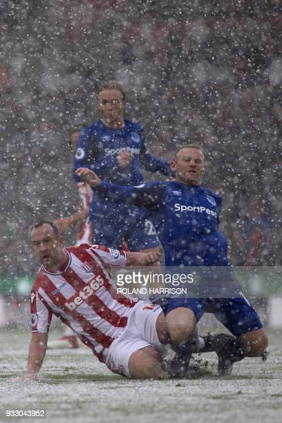 Everton's English striker Wayne Rooney is tackled by Stoke City's Scottish midfielder Charlie Adam during the English Premier League football match...