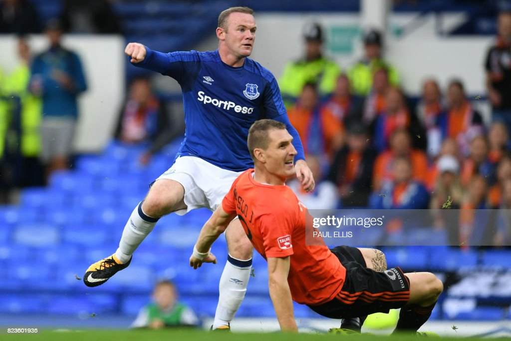 Everton's English striker Wayne Rooney (L) takes a shot at goal as MFK Ruzomberok's Jan Maslo blocks during the UEFA Europa League third qualifying round, Game 1 match between Everton and Ruzomberok at Goodison Park football stadium in Liverpool on July 27, 2017. / AFP PHOTO / Paul ELLIS