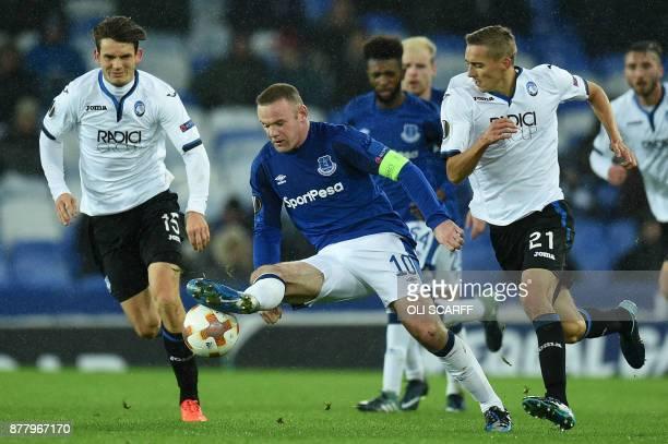 TOPSHOT Everton's English striker Wayne Rooney vies with Atalanta's Netherlands midfielder Marten de Roon and Atalanta's Belgium defender Timothy...