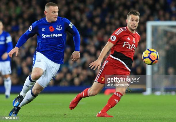 Everton's English striker Wayne Rooney vies with Watford's English mifielder Tom Cleverley during the English Premier League football match between...