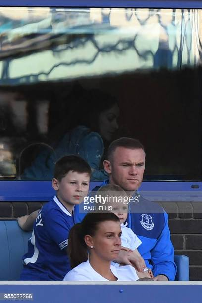 Everton's English striker Wayne Rooney watches from the stands with wife Colleen and children during the English Premier League football match...
