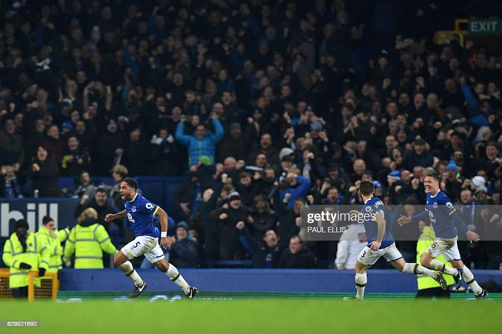 Everton's English-born Welsh defender Ashley Williams (L) celebrates scoring his team's second goal during the English Premier League football match between Everton and Arsenal at Goodison Park in Liverpool, north west England on December 13, 2016. / AFP / Paul ELLIS / RESTRICTED TO EDITORIAL USE. No use with unauthorized audio, video, data, fixture lists, club/league logos or 'live' services. Online in-match use limited to 75 images, no video emulation. No use in betting, games or single club/league/player publications. /