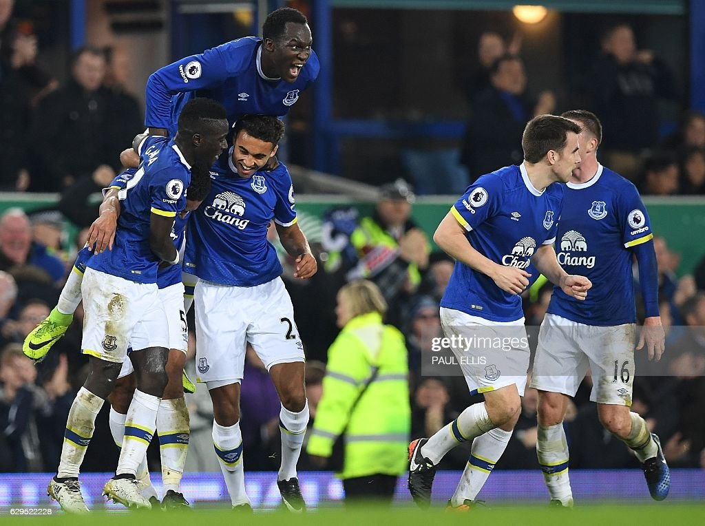 Everton's English-born Welsh defender Ashley Williams is mobbed by teammates as he celebrates scoring his team's second goal during the English Premier League football match between Everton and Arsenal at Goodison Park in Liverpool, north west England on December 13, 2016. Everton won the match 2-1. / AFP / Paul ELLIS / RESTRICTED TO EDITORIAL USE. No use with unauthorized audio, video, data, fixture lists, club/league logos or 'live' services. Online in-match use limited to 75 images, no video emulation. No use in betting, games or single club/league/player publications. /