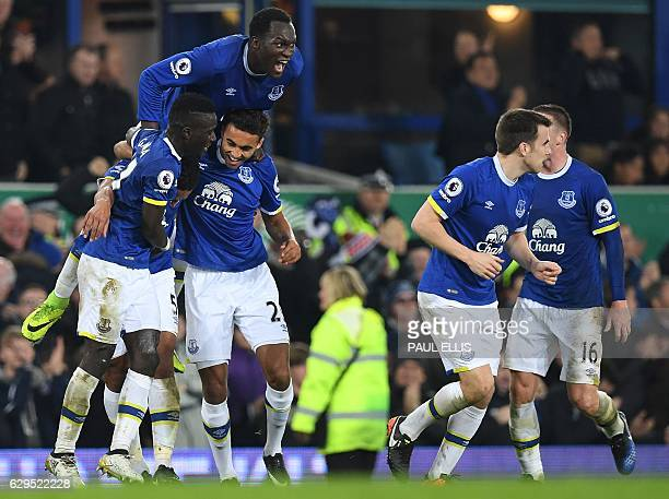 Everton's Englishborn Welsh defender Ashley Williams is mobbed by teammates as he celebrates scoring his team's second goal during the English...