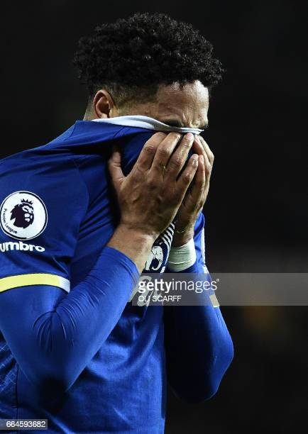 Everton's Englishborn Welsh defender Ashley Williams reacts as he leaves the pitch after coneceding a penalty by handball during the English Premier...
