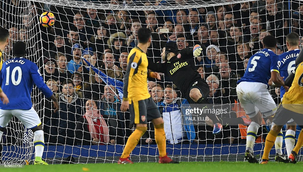 Everton's English-born Welsh defender Ashley Williams (2R) scores his team's second goal past Arsenal's Czech goalkeeper Petr Cech during the English Premier League football match between Everton and Arsenal at Goodison Park in Liverpool, north west England on December 13, 2016. Everton won the match 2-1. / AFP / Paul ELLIS / RESTRICTED TO EDITORIAL USE. No use with unauthorized audio, video, data, fixture lists, club/league logos or 'live' services. Online in-match use limited to 75 images, no video emulation. No use in betting, games or single club/league/player publications. /