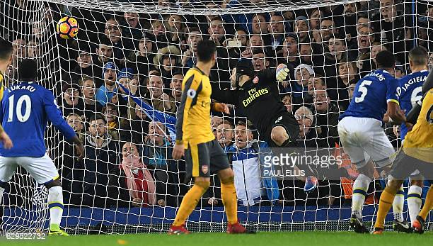 Everton's Englishborn Welsh defender Ashley Williams scores his team's second goal past Arsenal's Czech goalkeeper Petr Cech during the English...