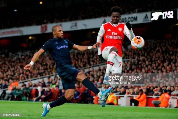 Everton's French Defender Djibril Sidibe challenges Arsenal's English striker Bukayo Saka during the English Premier League football match between...