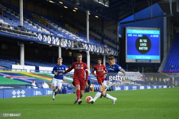 Everton's French defender Lucas Digne challenges Liverpool's English midfielder Jordan Henderson during the English Premier League football match...