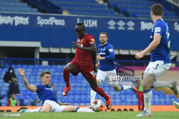 Everton's French defender Lucas Digne tackles Liverpool's Senegalese striker Sadio Mane and recieves a yellow card for the challenge during the...