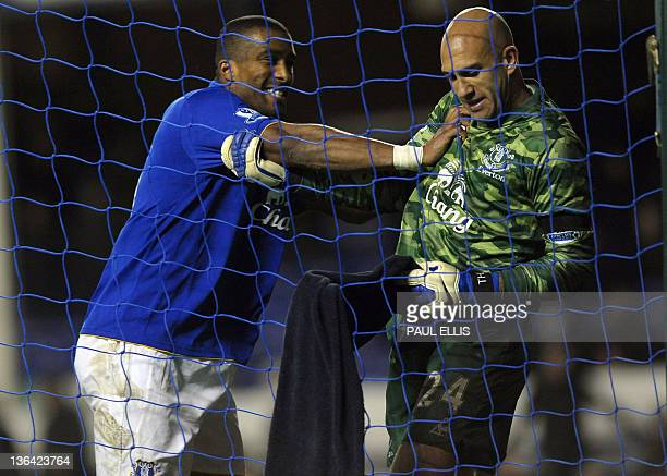 Everton's French defender Sylvain Distin congratulates Everton's American goalkeeper Tim Howard after the keeper scored from his own goal area during...