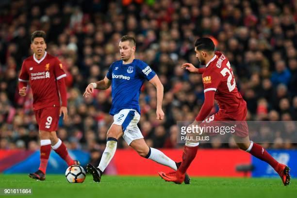 Everton's French midfielder Morgan Schneiderlin runs with the ball between Liverpool's German midfielder Emre Can and Liverpool's Brazilian...