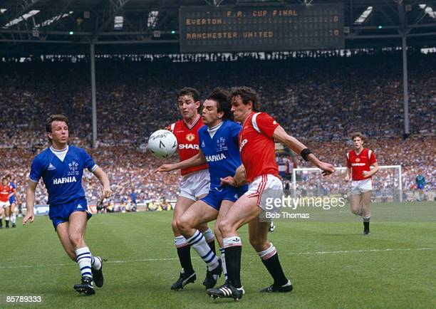 Everton's Graeme Sharp is stopped by Manchester United defenders Arthur Albiston and Kevin Moran with Everton's Trevor Steven looking on during the...
