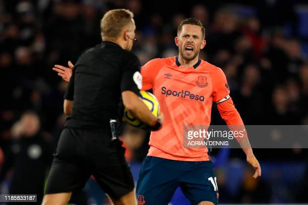 Everton's Icelandic midfielder Gylfi Sigurdsson appeals to the real referee after the VAR gives a late goal to Leicester City's Nigerian striker...