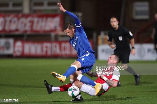 Everton's Icelandic midfielder Gylfi Sigurdsson is tackled by Fleetwood Town's Irish midfielder Glenn Whelan during the English League Cup third...