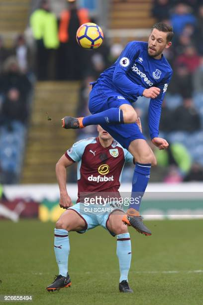 Everton's Icelandic midfielder Gylfi Sigurdsson jumps to control the ball in front of Burnley's English midfielder Ashley Westwood during the English...