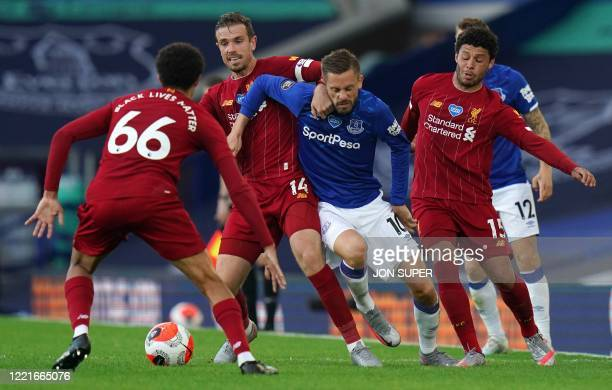 Everton's Icelandic midfielder Gylfi Sigurdsson vies for the ball against Liverpool's English midfielder Alex Oxlade-Chamberlain and Liverpool's...