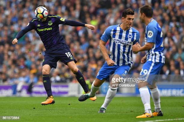 Everton's Icelandic midfielder Gylfi Sigurdsson vies with Brighton's English defender Lewis Dunk and Brighton's Austrian defender Markus Suttner...