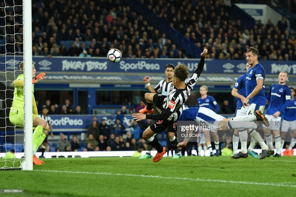 Everton's Irish defender Seamus Coleman dives to clear the ball fromthe path of Newcastle United's English striker Dwight Gayle (C) during the English Premier League football match between Everton and Newcastle United at Goodison Park in Liverpool, north west England on April 23, 2018. (Photo by Oli SCARFF / AFP) / RESTRICTED TO EDITORIAL USE. No use with unauthorized audio, video, data, fixture lists, club/league logos or 'live' services. Online in-match use limited to 75 images, no video emulation. No use in betting, games or single club/league/player publications. /