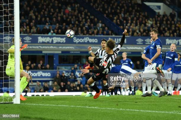 Everton's Irish defender Seamus Coleman dives to clear the ball fromthe path of Newcastle United's English striker Dwight Gayle during the English...
