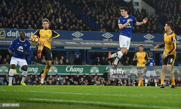 Everton's Irish defender Seamus Coleman heads the ball past Arsenal's Spanish defender Nacho Monreal to score his team's first goal during the...