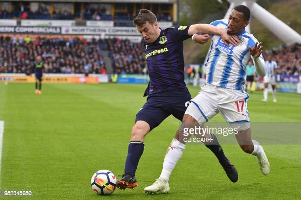 Everton's Irish defender Seamus Coleman vies with Huddersfield Town's Dutch midfielder Rajiv van La Parra during the English Premier League football...
