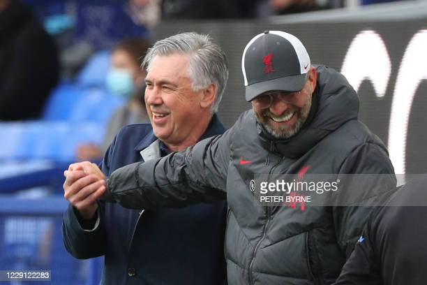 Everton's Italian head coach Carlo Ancelotti and Liverpool's German manager Jurgen Klopp share a light moment during the English Premier League...