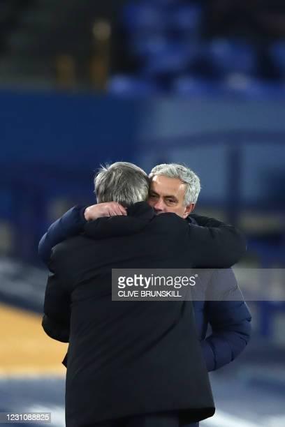 Everton's Italian head coach Carlo Ancelotti and Tottenham Hotspur's Portuguese head coach Jose Mourinho embrace at the final whistle during the...