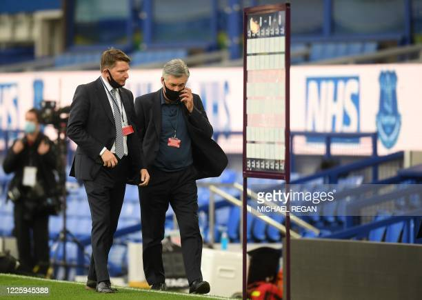 Everton's Italian head coach Carlo Ancelotti wearing a face mask or covering due to the COVID-19 pandemic, walks on the pitch ahead of the English...