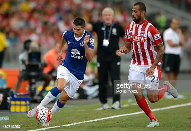 Everton's Kevin Mirallas dribbles the ball past Stoke City's Dionatan Teixeira during their Barclays Asia Trophy football match at Singapore National...