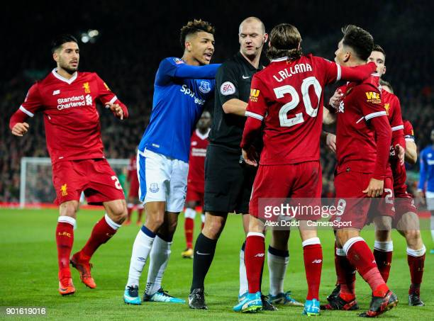 Everton's Mason Holgate and Liverpool's Roberto Firmino have an altercation while referee Robert Madley tries to separate the pair during the...