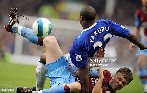 Everton's Nigerian forward Yakubu falls onto Aston Villa's Danish defender Martin Laursen during the English Premier League football match at...