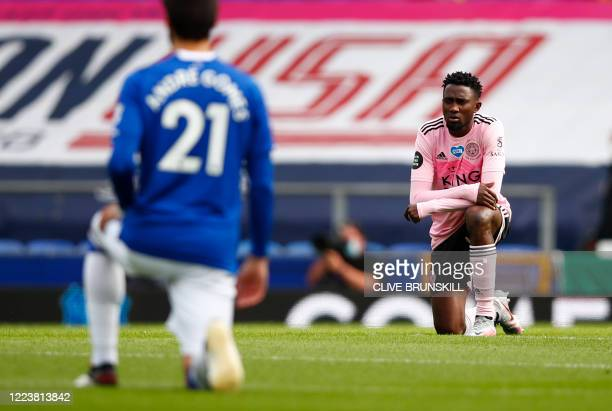 Everton's Portuguese midfielder André Gomes and Leicester City's Nigerian midfielder Wilfred Ndidi kneel in support of the Black Lives Matter...