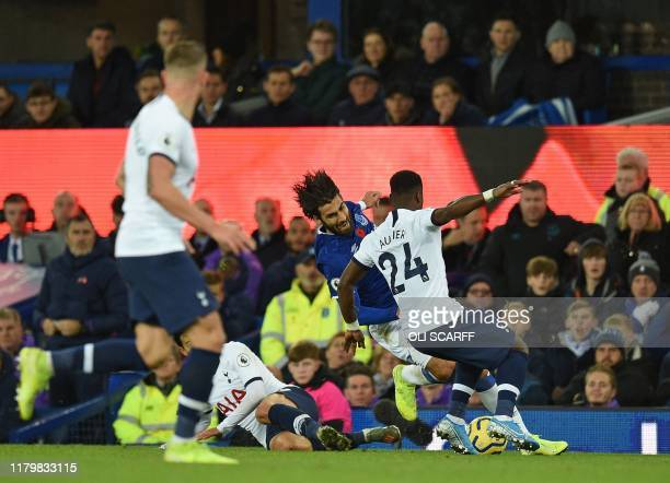 Everton's Portuguese midfielder André Gomes is brought down after being clipped by Tottenham Hotspur's South Korean striker Son Heung-Min and a...