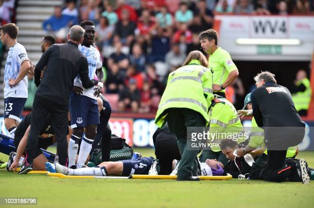 Everton's Senegalese midfielder Idrissa Gueye and Everton's English defender Michael Keane receive treatment after clashing going for a header during...
