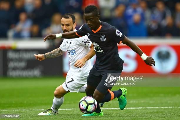 Everton's Senegalese midfielder Idrissa Gueye vies with Swansea City's English midfielder Leon Britton during the English Premier League football...