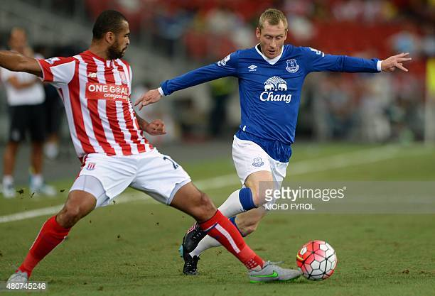 Everton's Tony Hibbert dribbles the ball past Stoke City's Dionatan Teixeira during their Barclays Asia Trophy football match at Singapore National...