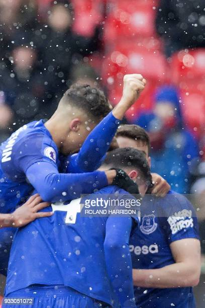Everton's Turkish striker Cenk Tosun celerates with teammates scoring the team's first goal during the English Premier League football match between...