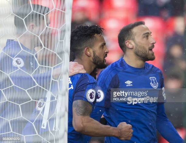 Everton's Turkish striker Cenk Tosun celerates with teammates scoring the team's second goal during the English Premier League football match between...