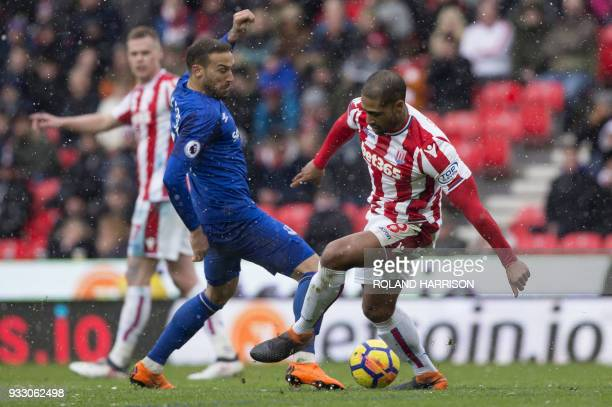 Everton's Turkish striker Cenk Tosun vies with Stoke City's English defender Glen Johnson during the English Premier League football match between...