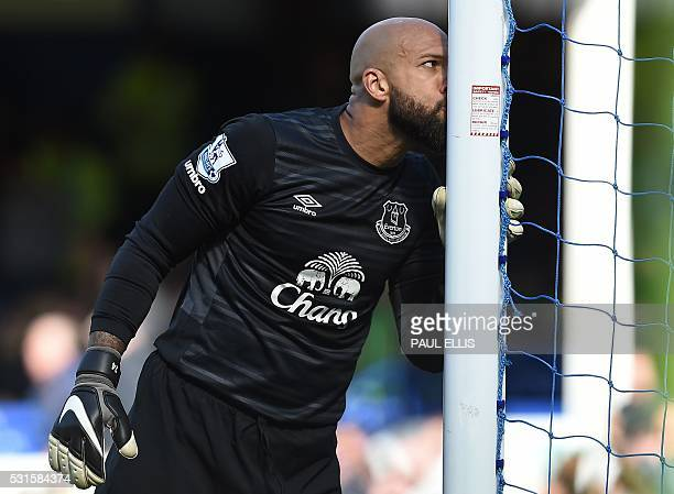 Everton's US goalkeeper Tim Howard kisses his goalpost at the final whistle during the English Premier League football match between Everton and...