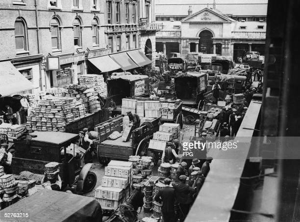 Every morning deliverymen stockboys and other workers unload delivery trucks and carts and load the stores of Covent Garden Market with crates and...
