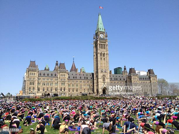Every Wednesday in summer, hundreds gather on the lawn of the federal government's Parliament Buildings in Ottawa, Canada for an outdoor group yoga...
