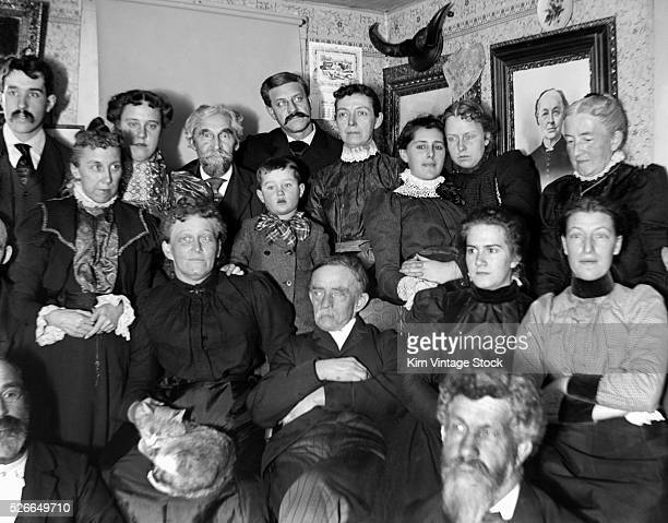 Everybody but one person looks away for a formal portrait in a Victorian parlor