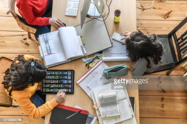 iedereen doet zijn werk bij houten bureau in woonkamer - werk privé balans stockfoto's en -beelden