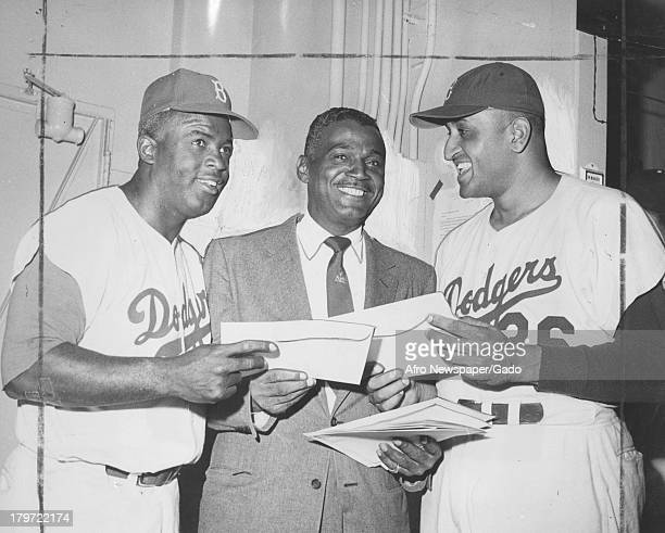 Everybody's happy as American baseball player Jackie Robinson formerly of the Brooklyn Dodgers and Don Newcombe each garner a handful of Schaefer...
