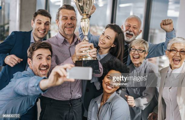everyone smile for a photo with a trophy! - trophy award stock pictures, royalty-free photos & images